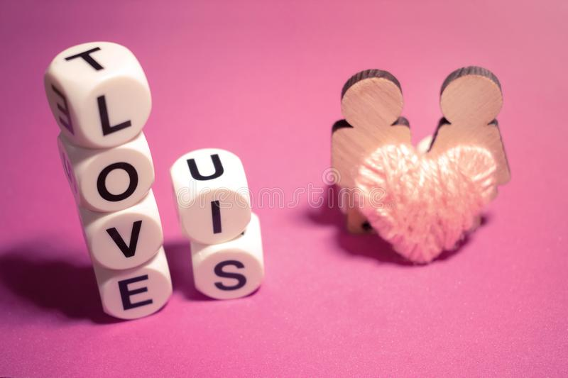 LOVE IS text word made with white plastic blocks, two wooden fig stock photos