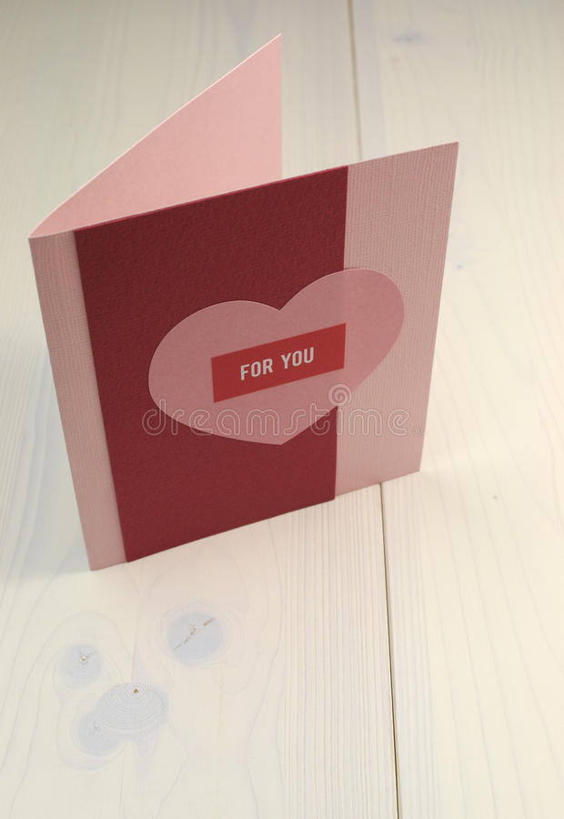 Love theme handmade gift card with heart and 'for you' message on white shabby chic table. Red and pink handmade gift card with heart and 'for you' message on royalty free stock photo