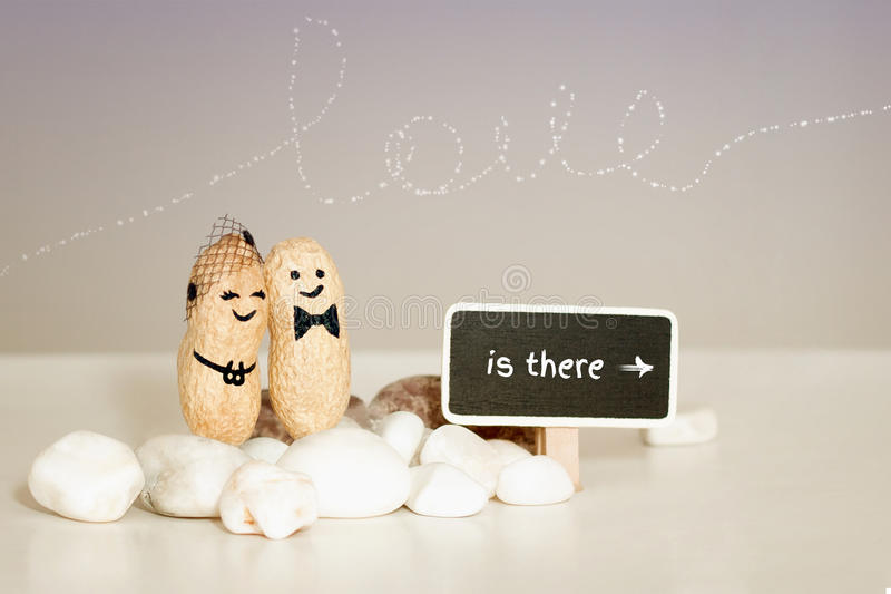 ` love is there`. Two peanuts with drawn faces hugging on pink vanilla background. royalty free stock photo