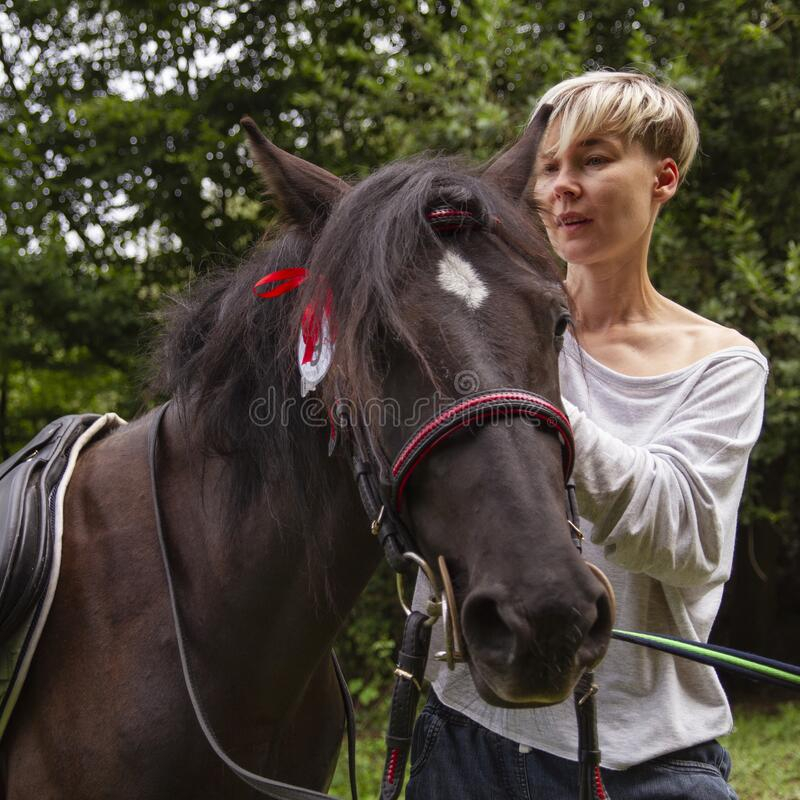 Closeup horse and woman outdoor walk. Love to the animals: closeup horse and woman, outdoor walk stock image