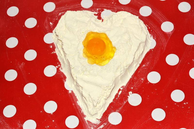 The love to bake it! egg yolk on heart flour. Love to bake it! egg yolk on heart flour royalty free stock images