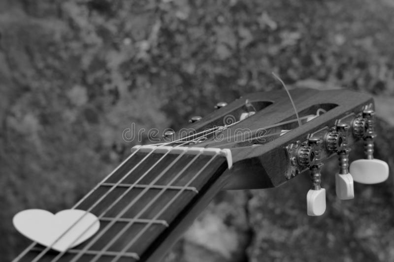 Love to Pick. A Guitar Headstock, Showing the Tuning Pegs and Machine Heads of the acoustic  Instrument with a Blurred Foreground Hand Holding a Love Heart Pick royalty free stock image