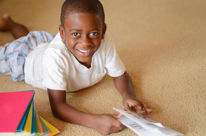 Love to Read. A young African American male laying on the floor reading a books royalty free stock photo