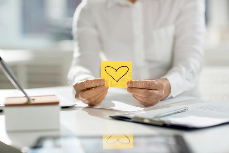 Love to work. Human hands holding yellow notepaper with heart shape over workplace stock photos