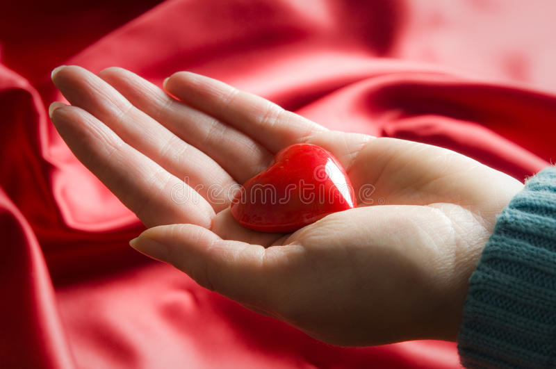 Love to you. Woman hand with red heart like a Valentine love concept stock image