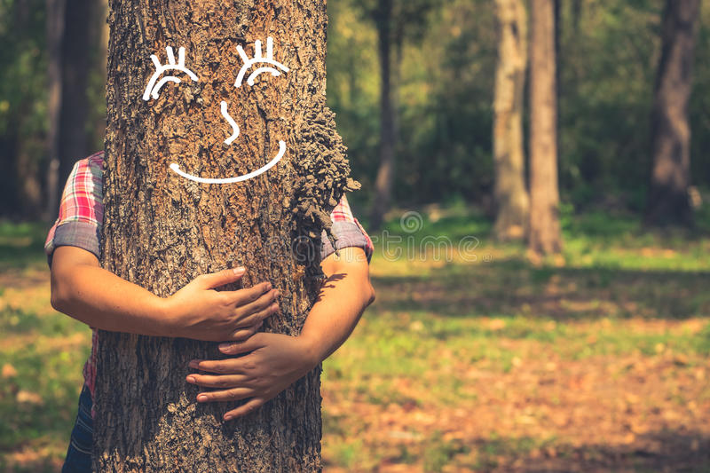 Love Tree. Love nature concept, woman give a hug behind tree trunk with drawing of tree's smile face stock image