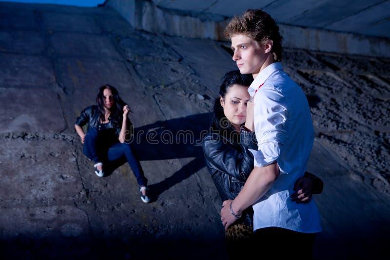 Love triangle. In night near concrete wall stock photo