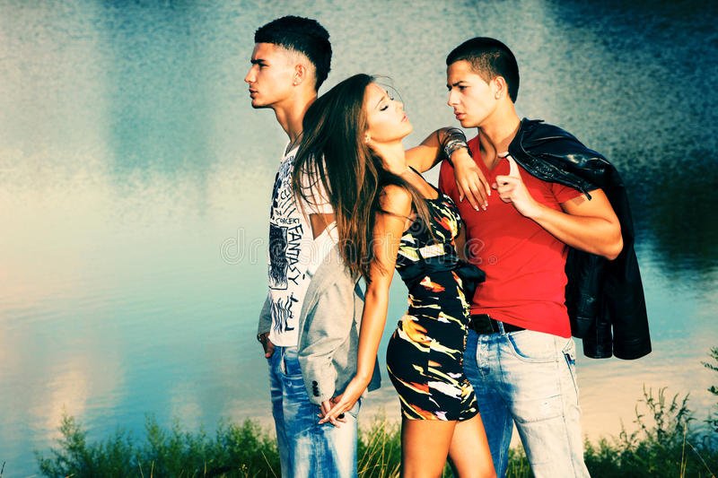 Love triangle. Two young men and young women on the beach at sunset royalty free stock photos