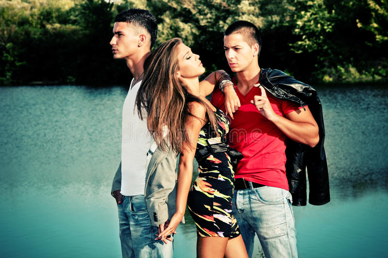 Love triangle. Young women with two young men, love triangle, outdoors shot stock photography