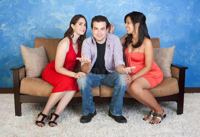 Love Triangle. Two women flirting with a handsome men on sofa royalty free stock photography