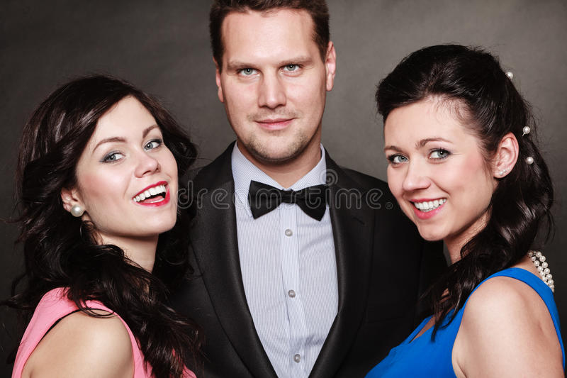 Love triangle or friendship. Portrait of smiling two women and one men wearing elegant clothes on black. Luxury party royalty free stock photography