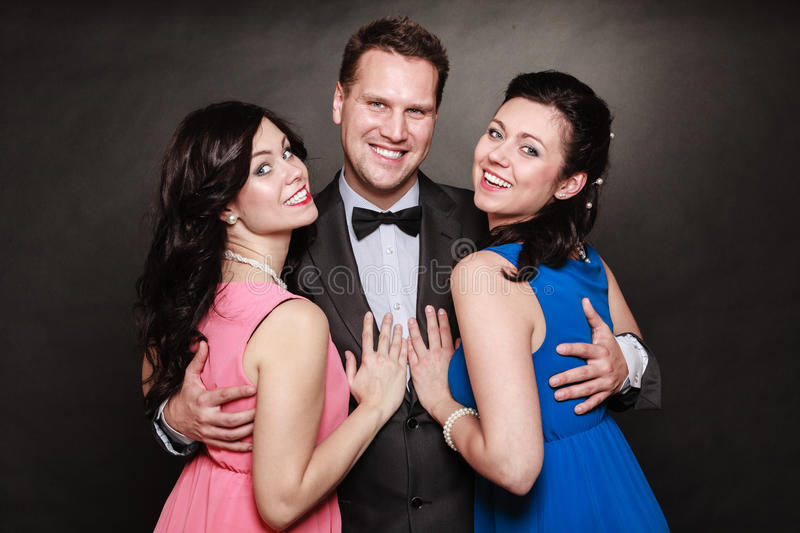 Love triangle or friendship. Portrait of smiling two women and one men wearing elegant clothes on black. Luxury party stock image