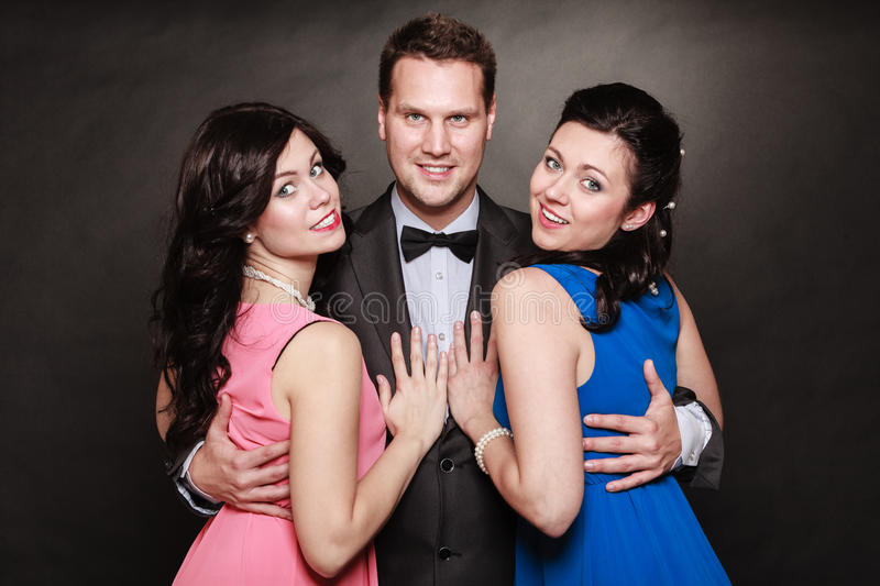 Love triangle or friendship. Portrait of smiling two women and one men wearing elegant clothes on black. Luxury party stock photography