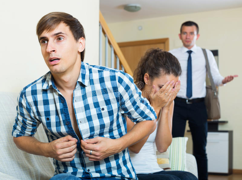 Love triangle: husband, wife and lover at domestic interior. Love triangle: adult husband, upset wife and lover at domestic interior stock images