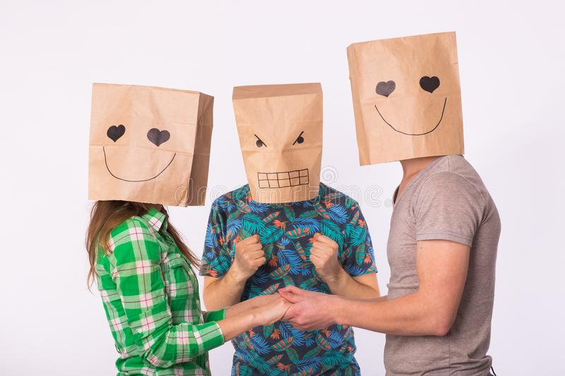 Love triangle, jealousy and unrequited love concept - woman and man with bags over heads holding hands and another man. Love triangle, jealousy and unrequited stock photo