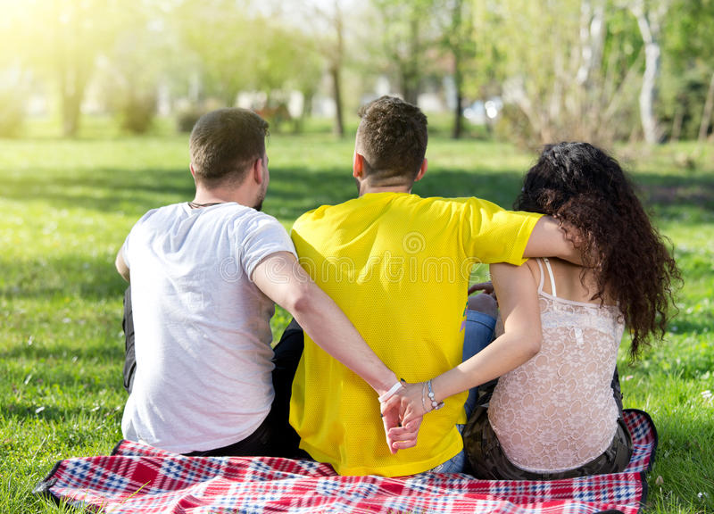 Love triangle in park. Girl with two boys, one hugging her and another one holding her hand behind his back. Love triangle stock photos