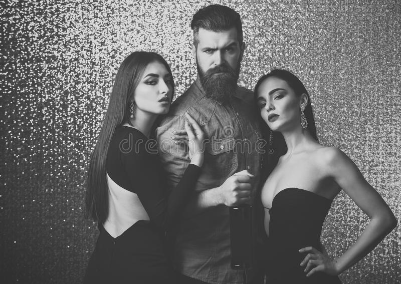 Love triangle, relationship, lifestyle. Girls and hipster with bottle of wine. Party, holidays celebration. Bad habit, alcohol addiction. Bearded men with stock image
