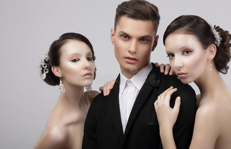 Love Triangle. Two Charming Women Hugging a Handsome Man stock photography