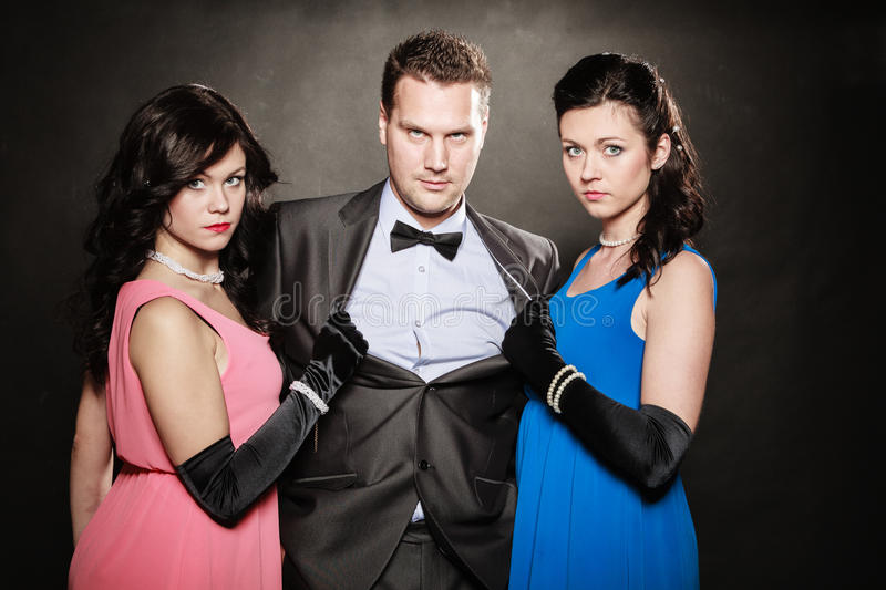 Love triangle. Two women and one man. Betrayal. Love triangle. Portrait of two women and one men wearing elegant clothes on black. Mistress and betrayal within stock photo