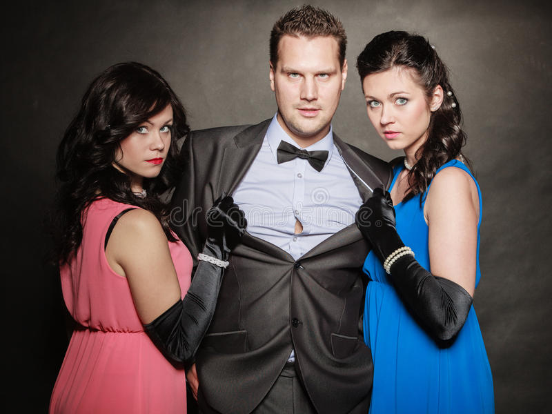 Love triangle. Two women and one man. Betrayal. Love triangle. Portrait of two women and one men wearing elegant clothes on black. Mistress and betrayal within stock image