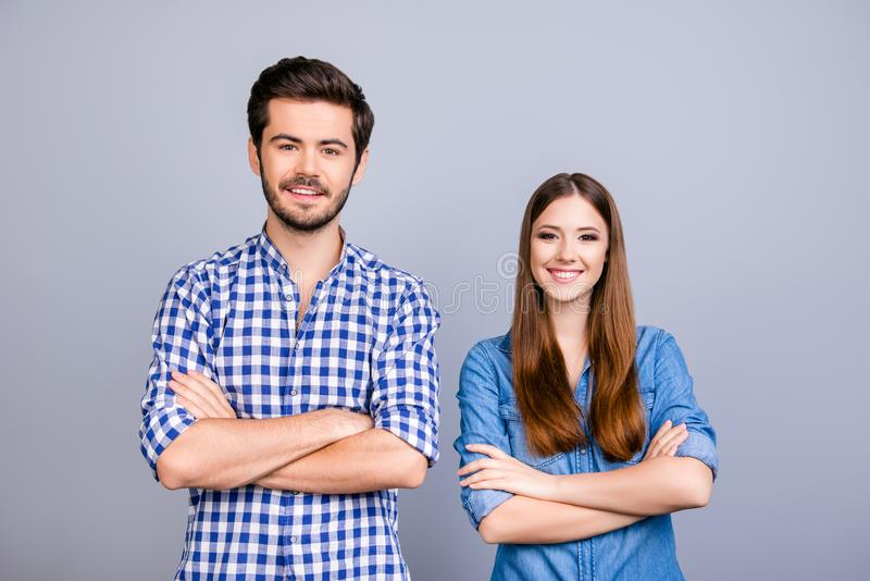 Love, trust, friendship, fun, happiness. Two cheerful young love. Rs are standing and smiling, wearing casual clothes, with crossed hands on the pure background royalty free stock image