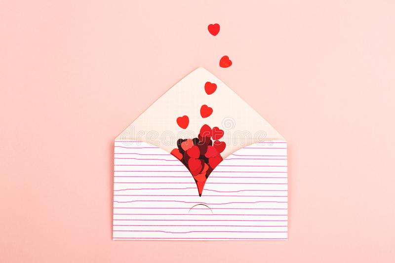 Envelope on pink background. Love or Valentine day background made with cute envelope and red heart shape confetti. Love letter or message concept. Pastel pink stock photo