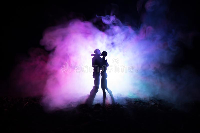 Love Valentine`s Day concept.Sillhouette of sweet young couple in love standing in the field and hugging on dark toned foggy backg stock images