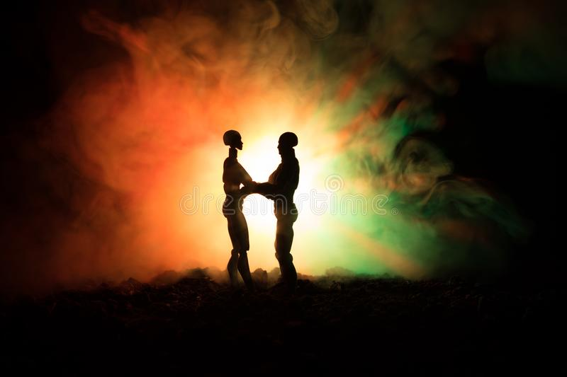 Love Valentine`s Day concept.Sillhouette of sweet young couple in love standing in the field and hugging on dark toned foggy backg royalty free stock photography