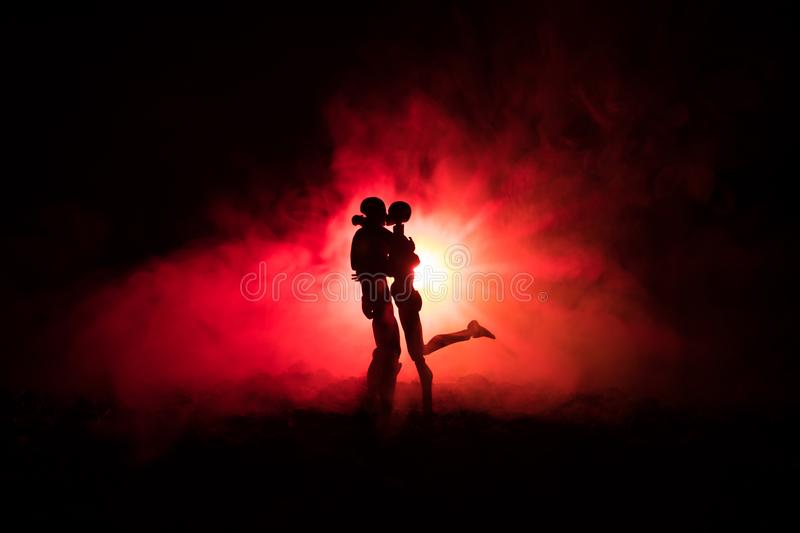 Love Valentine`s Day concept.Sillhouette of sweet young couple in love standing in the field and hugging on dark toned foggy backg stock image