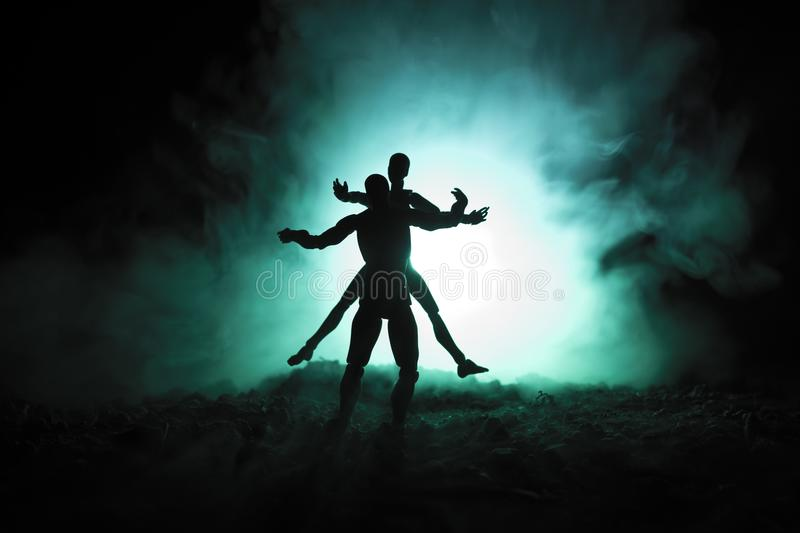 Love Valentine`s Day concept.Sillhouette of sweet young couple in love standing in the field and hugging on dark toned foggy backg stock photography