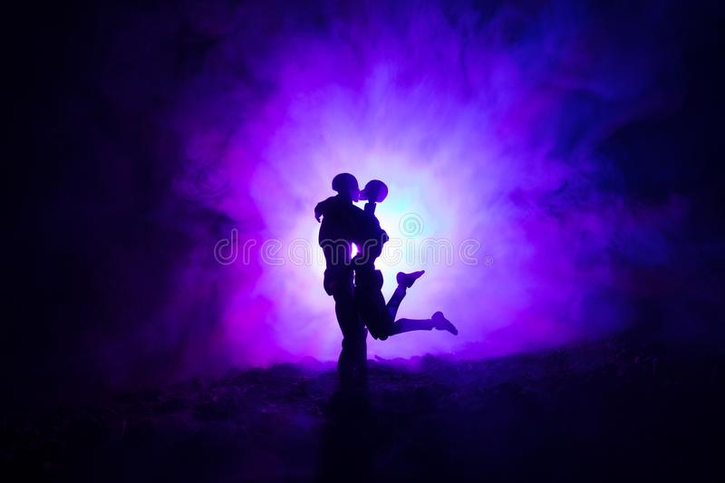 Love Valentine`s Day concept.Sillhouette of sweet young couple in love standing in the field and hugging on dark toned foggy backg stock photos