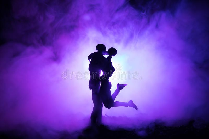 Love Valentine`s Day concept.Sillhouette of sweet young couple in love standing in the field and hugging on dark toned foggy backg royalty free stock photos