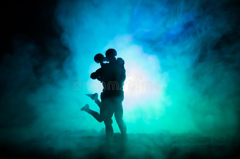 Love Valentine`s Day concept.Sillhouette of sweet young couple in love standing in the field and hugging on dark toned foggy backg. Round. Decoration with doll stock photography