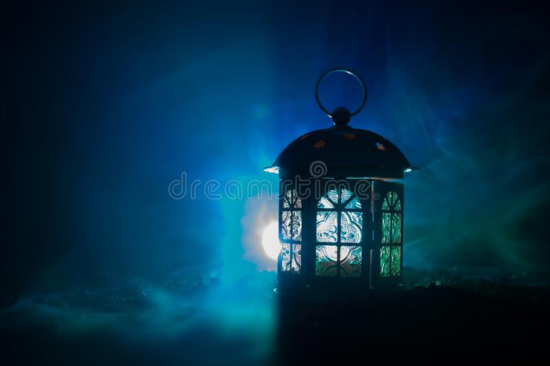 Love Valentine`s Day greeting card decoration photo. Candle lighting lamp lantern glowing on dark colorful foggy background. stock photography