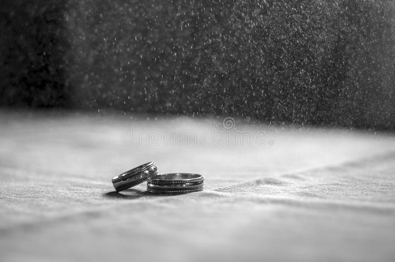 Love, Valentine`s day and wedding concept. Two wedding rings with man and woman hands blurred in the background. Selective focus stock photo