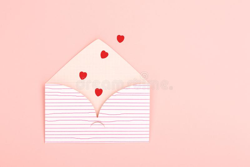 Envelope on pink background. Love or Valentines day background made with cute envelope and red heart shape confetti. Love letter or message concept. Pastel pink stock images