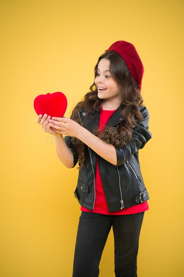Love. valentines day. child on yellow wall. small girl kid with long curly hair. happy girl in french beret and leather. Jacket. parisian fashion girl hold red stock photos