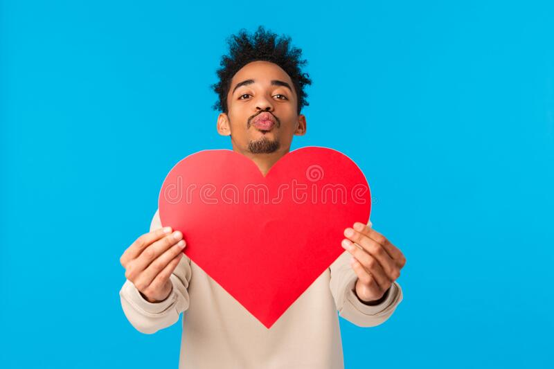 Love, valentines day and relationship concept. Cute boyfriend african american guy with afro haircut, give valentine. Card big heart and folding lips for kiss royalty free stock photography