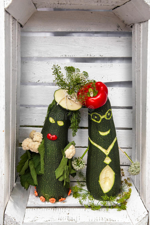 Love vege. A funny pair of vegetables in love in white wooden box stock images