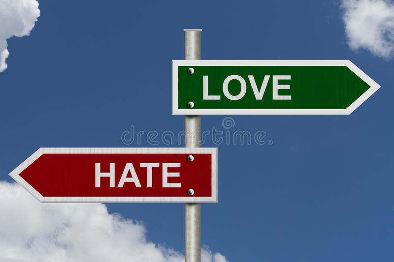 Love versus Hate. Red and green street signs with blue sky with words Love and Hate royalty free stock photography