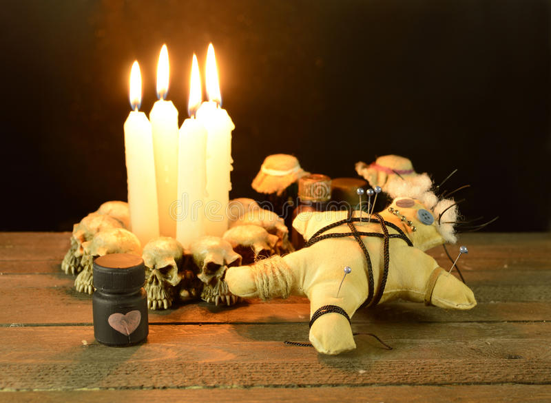 Love voodoo ritual. Pierced voodoo doll with love potion bottles on wooden background royalty free stock images