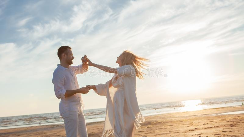 Love, waiting for the baby. Couple, pregnant woman and man, in white flying clothes, walk, hold hands, dance. royalty free stock photo