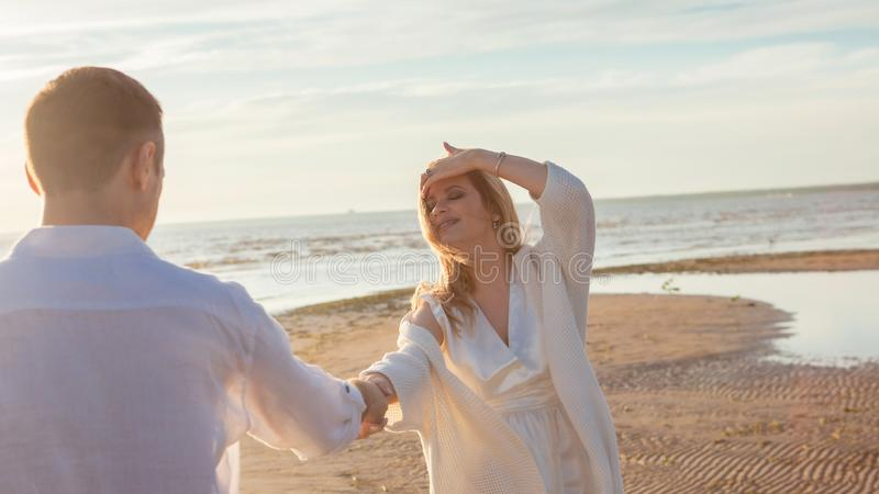 Love, waiting for the baby. Couple, pregnant woman and man, in white flying clothes, walk, hold hands, hug the tummy. Love, waiting for the baby. A young royalty free stock image