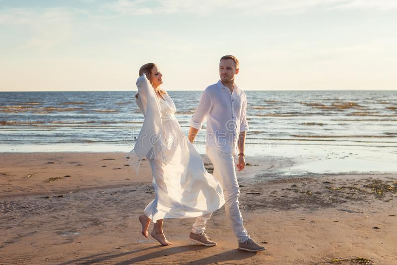 Love, waiting for the baby. Couple, pregnant woman and man, in white flying clothes, walk, hold hands, hug the tummy. Love, waiting for the baby. A young royalty free stock photo