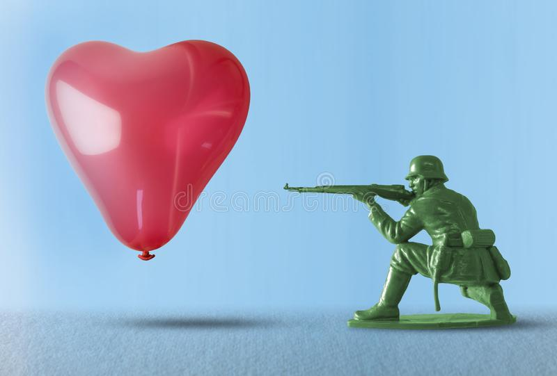 Heart balloon as a target for a soldier shooting a gun - concept for love and war stock images