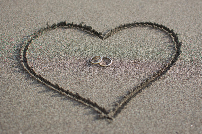 Love and wedding on the beach. Wedding rings on the beach sand, surrounded by the heart. Symbol of love and devotion royalty free stock photos