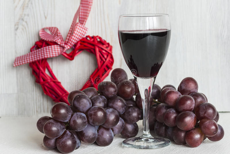 Love and wine. Glass of red wine, grapes and shape heart on light wooden background royalty free stock image