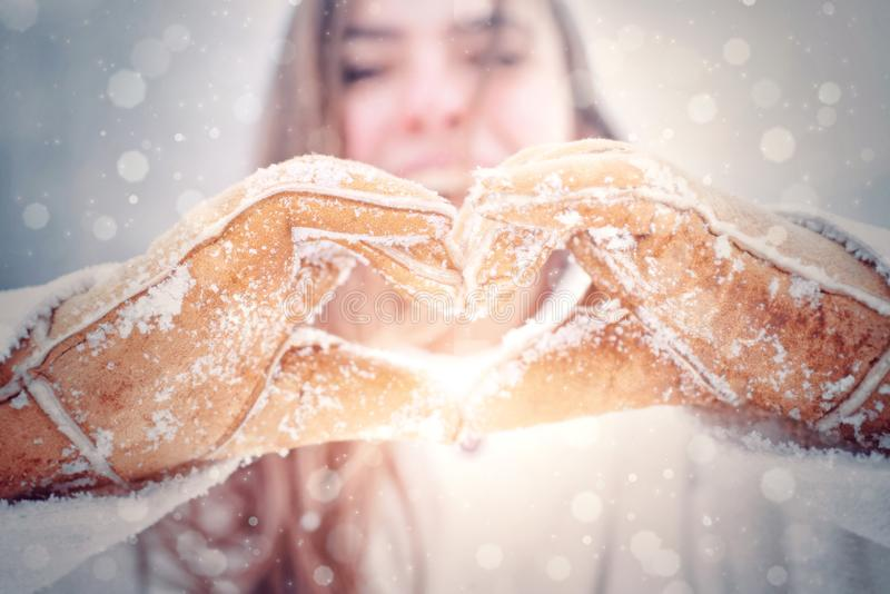 Love winter. Happy woman shows heart. Woman hands in winter gloves Heart symbol shaped Lifestyle and Feelings concept stock images