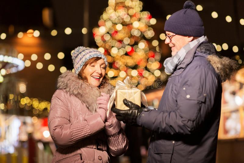 Happy senior couple with gift at christmas market. Love, winter holidays and people concept - happy senior couple with gift at christmas market on town hall stock image