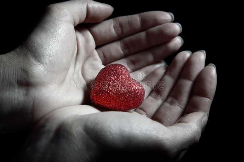 Love. Woman hands holding a small heart as a symbol of love royalty free stock photos